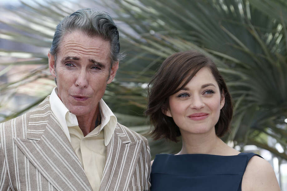 "French actress Marion Cotillard (R) and US tattoo artist and actor Mark Mahoney pose on May 20, 2013 during a photocall for the film ""Blood Ties"" presented Out of Competition at the 66th edition of the Cannes Film Festival in Cannes. Cannes, one of the world's top film festivals, opened on May 15 and will climax on May 26 with awards selected by a jury headed this year by Hollywood legend Steven Spielberg. Photo: VALERY HACHE, AFP/Getty Images / 2013 AFP"