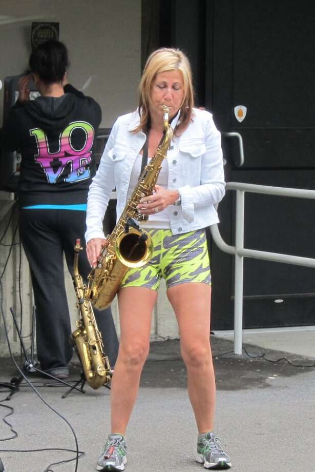 Under the SPAC box office roof overhang, Saxophone Lady calls the final stretch across the bridge.