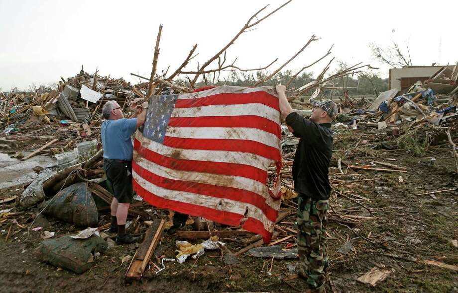 Clark Gardner, at left, and another man place an American flag on debris in a neighborhood off of Telephone Road in Moore, Okla., after a tornado moved through the area on Monday, May 20, 2013. (AP Photo/ The Oklahoman, Bryan Terry) Photo: BRYAN TERRY, Associated Press / The Oklahoman