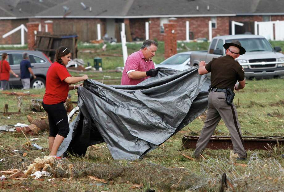 A man and a woman assist a state trooper carry a large tarp to cover a tornado victim found in a field across the street from the Madison Place Addition, near SE 8 and Tower in Moore, on Monday, May 20, 2013.    (AP Photo/ The Oklahoman, Jim Beckel) Photo: Jim Beckel, Associated Press / The Oklahoman