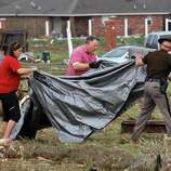 A man and a woman assist a state trooper carry a large tarp to cover a tornado victim found in a field across the street from the Madison Place Addition, near SE 8 and Tower in Moore, on Monday, May 20, 2013.    (AP Photo/ The Oklahoman, Jim Beckel)