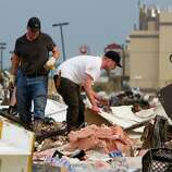 People search the debris near Telephone Road and SW 4th Street in Moore, Okla. after a tornado on Monday, May 20, 2013. (AP Photo/Alonzo Adams)