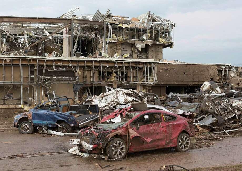 The Moore Medical Center and vehicles lay damaged after a tornado moves through Moore, Okla. on Monday, May 20, 2013. (AP Photo/Alonzo Adams) Photo: Alonzo Adams, Associated Press / FR159426 AP