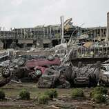 MOORE, OK- MAY 20:   Flipped vehicles are piled up outside the heavily damaged Moore Medical Center after a powerful tornado ripped through the area on May 20, 2013 in Moore, Oklahoma. The tornado, reported to be at least EF4 strength and two miles wide, touched down in the Oklahoma City area on Monday killing at least 51 people.