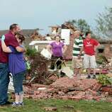 Glenn Rusk hugs his neighbor Sherie Loman outside her home north of Briarwood Elementary School after a tornado moved through the area, in Moore, Okla., Monday, May 20, 2013.