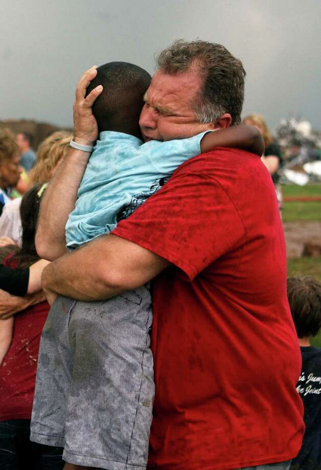 A teacher hugs a child at Briarwood Elementary school after a tornado destroyed the school in south Oklahoma City, Monday, May 20, 2013. A monstrous tornado roared through the Oklahoma City suburbs, flattening entire neighborhoods with winds up to 200 mph, setting buildings on fire and landing a direct blow on an elementary school. Photo: The Oklahoman, Paul Hellstern