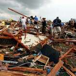 Workers look for victims under debris from a tornado that passed across south Oklahoma City, Monday, May 20, 2013. A monstrous tornado roared through the Oklahoma City suburbs, flattening entire neighborhoods with winds up to 200 mph, setting buildings on fire and landing a direct blow on an elementary school.