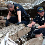 Moore police dig through the rubble of the Plaza Towers Elementary School following a tornado in Moore, Okla., Monday, May 20, 2013. A tornado as much as a mile (1.6 kilometers) wide with winds up to 200 mph (320 kph) roared through the Oklahoma City suburbs Monday, flattening entire neighborhoods, setting buildings on fire and landing a direct blow on an elementary school.