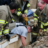 Rescue workers dig through the rubble of a collapsed wall at the Plaza Tower Elementary School to free trapped students in Moore, Okla., following a tornado Monday, May 20, 2013. A tornado as much as a mile (1.6 kilometers) wide with winds up to 200 mph (320 kph) roared through the Oklahoma City suburbs Monday, flattening entire neighborhoods, setting buildings on fire and landing a direct blow on an elementary school.