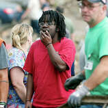 Onlookers watch as children are pulled from the rubble of the Plaza Towers Elementary School following a tornado in Moore, Okla., Monday, May 20, 2013. A tornado as much as a mile (1.6 kilometers) wide with winds up to 200 mph (320 kph) roared through the Oklahoma City suburbs Monday, flattening entire neighborhoods, setting buildings on fire and landing a direct blow on an elementary school.