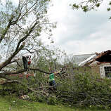 Volunteers chain saw a fallen tree knocked down by a tornado May 20, 2013 near Shawnee, Oklahoma. A series of tornados moved across central Oklahoma May 19, killing two people and injuring at least 21.