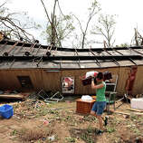 A volunteer helps clean up Jean McAdams' mobile home after it was overturned by a tornado May 20, 2013 near Shawnee, Oklahoma. A series of tornados moved across central Oklahoma May 19, killing two people and injuring at least 21.