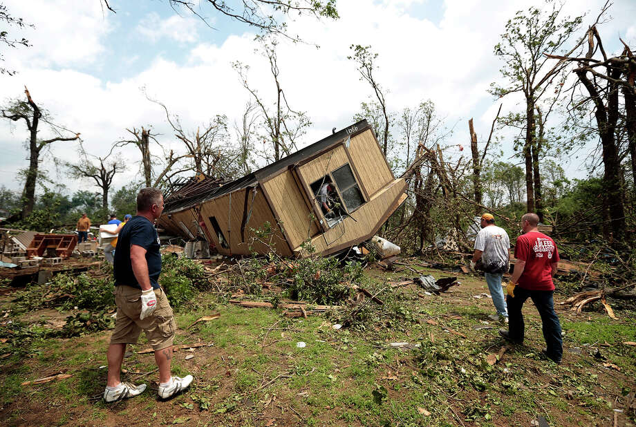 Volunteers help clean out Jean McAdams' mobile home after it was overturned by a tornado May 20, 2013 near Shawnee, Oklahoma. A series of tornados moved across central Oklahoma May 19, killing two people and injuring at least 21. Photo: Brett Deering, Getty Images / 2013 Getty Images