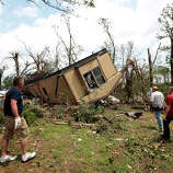 Volunteers help clean out Jean McAdams' mobile home after it was overturned by a tornado May 20, 2013 near Shawnee, Oklahoma. A series of tornados moved across central Oklahoma May 19, killing two people and injuring at least 21.