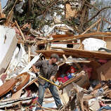 Zach Champion digs through the rubble of his mobile home for his belongings, Monday, May 20, 2013, in the Steelman Estates Mobile Home Park, destroyed in Sunday's tornado, near Shawnee, Okla.