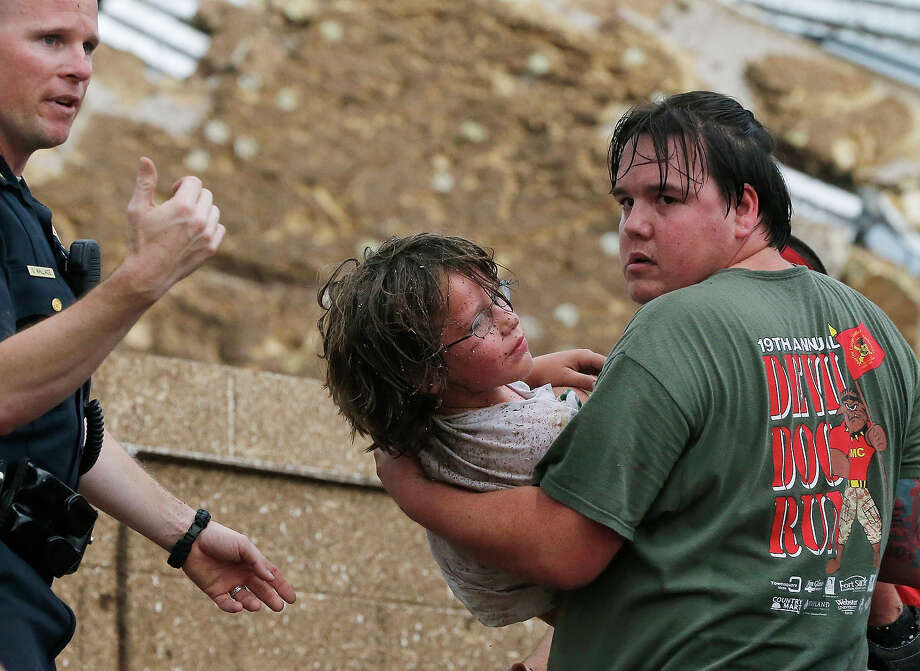 A child is carried from the rubble of the Plaza Towers Elementary School following a tornado in Moore, Okla., Monday, May 20, 2013. A tornado as much as a mile (1.6 kilometers) wide with winds up to 200 mph (320 kph) roared through the Oklahoma City suburbs Monday, flattening entire neighborhoods, setting buildings on fire and landing a direct blow on an elementary school. Photo: Sue Ogrocki, ASSOCIATED PRESS / AP2013