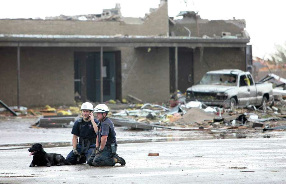 Searchers rest outside the Briarwood Elementary School after the tornado destroyed the school , Monday,  May 20, 2013. (AP Photo/ The Oklahoman,  David McDaniel) Photo: David McDaniel, Associated Press / The Oklahoman