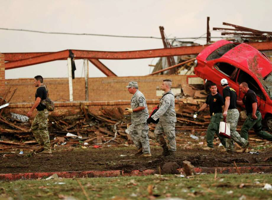 Workers walk past the rubble of Plaza Towers Elementary School after a tornado moved through Moore, Okla., Monday, May 20, 2013. (AP Photo Sue Ogrocki) Photo: Sue Ogrocki, Associated Press / AP