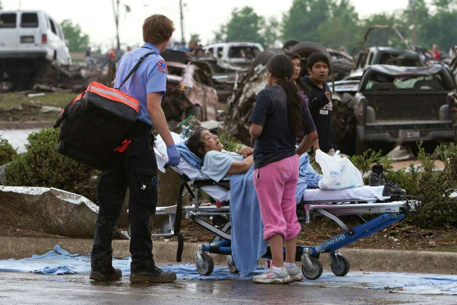 A Moore Medical Center patient sits in the parking lot after a tornado damaged the hospital in Moore, Okla. on Monday, May 20, 2013. (AP Photo/Alonzo Adams) Photo: Alonzo Adams, Associated Press / FR159426 AP