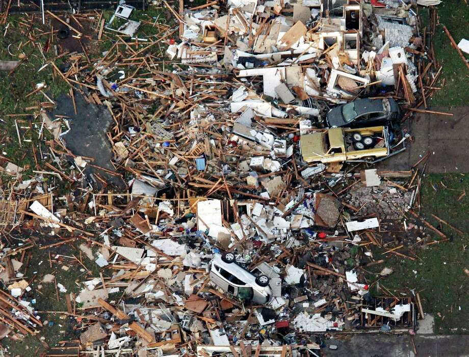 This aerial photo shows the remains of houses in Moore, Okla., following a tornado Monday, May 20, 2013. A tornado roared through the Oklahoma City suburbs Monday, flattening entire neighborhoods, setting buildings on fire and landing a direct blow on an elementary school. (AP Photo/Steve Gooch) Photo: Steve Gooch, Associated Press / AP