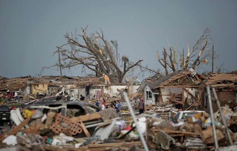 MOORE, OK - MAY 20:  People assess the damage after a powerful tornado ripped through the area on May 20, 2013 in Moore, Oklahoma. The tornado, reported to be at least EF4 strength and two miles wide, touched down in the Oklahoma City area on Monday killing at least 51 people. Photo: Brett Deering, Getty Images / 2013 Getty Images