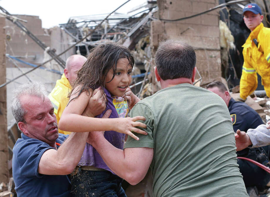 A child is pulled from the rubble of the Plaza Towers Elementary School in Moore, Okla., and passed along to rescuers Monday, May 20, 2013. A tornado as much as a mile (1.6 kilometers) wide with winds up to 200 mph (320 kph) roared through the Oklahoma City suburbs Monday, flattening entire neighborhoods, setting buildings on fire and landing a direct blow on an elementary school. Photo: Sue Ogrocki, ASSOCIATED PRESS / THE ASSOCIATED PRESS2013