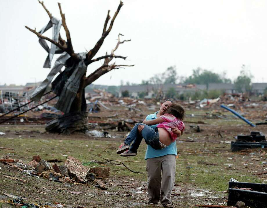 A woman carries a child through a field near the collapsed Plaza Towers Elementary School in Moore, Okla., Monday, May 20, 2013.  A tornado as much as a mile wide with winds up to 200 mph roared through the Oklahoma City suburbs Monday, flattening entire neighborhoods, setting buildings on fire and landing a direct blow on an elementary school. (AP Photo Sue Ogrocki) Photo: Sue Ogrocki, STF / AP