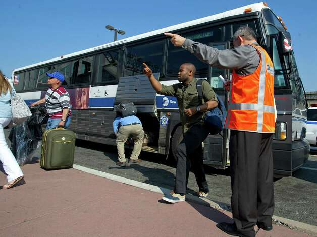 Commuters exiting a bus from Bridgeport get directions to the appropriate platform from customer service representatives in orange vests at the train station in Stamford, Conn., on Tuesday, May 21, 2013. Photo: Lindsay Perry / Stamford Advocate