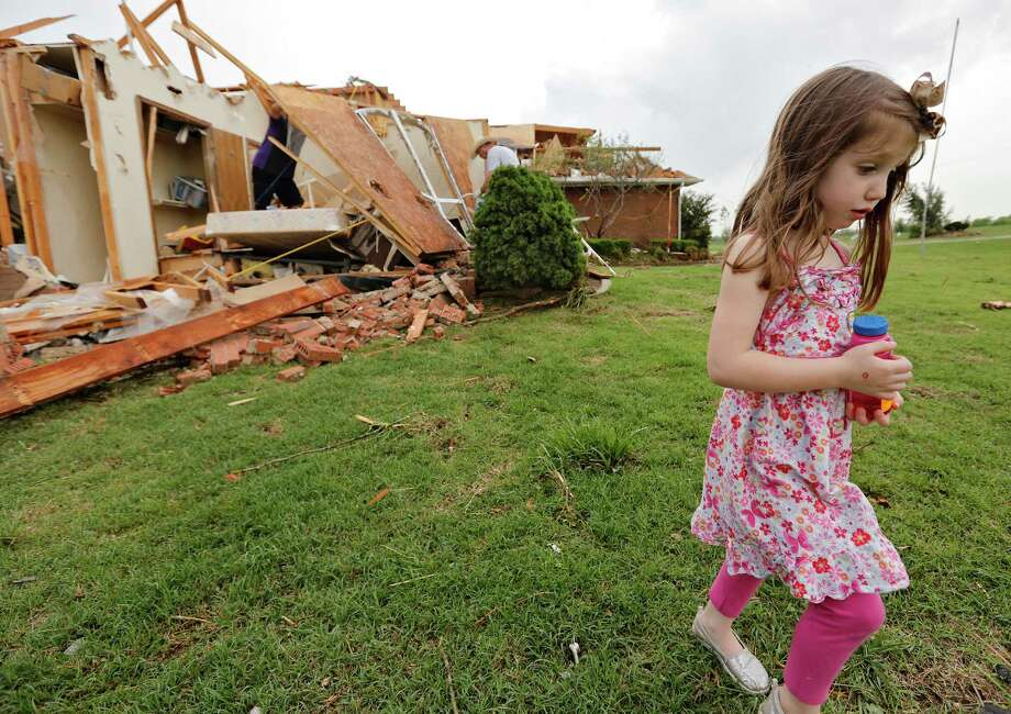 Magen Stanley, 5, walks away from her grandparents destroyed home after a tornado hit the area near 149th and Drexel on Monday, May 20, 2013 in Oklahoma City, Okla.  (AP Photo/ The Oklahoman, Chris Landsberger) Photo: CHRIS LANDSBERGER, Associated Press / The Oklahoman