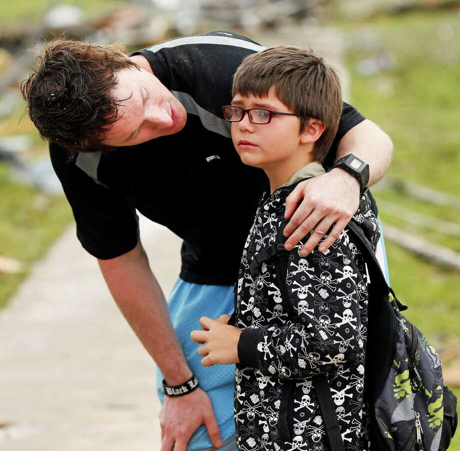 Briarwood Elementary P.E. teacher Mike Murphy comforts Aiden Stuck, 7, as he waits for his mother at the school after a tornado destroyed Briarwood Elementary and struck south Oklahoma City and Moore, Okla., Monday, May 20, 2013.(AP Photo/ The Oklahoman, Nate Billings) Photo: NATE BILLINGS, Associated Press / The Oklahoman