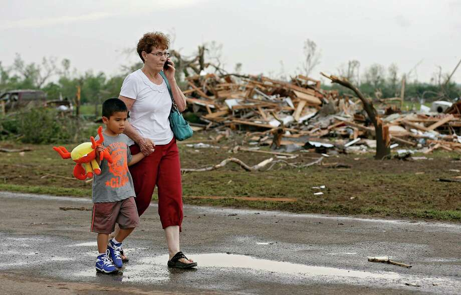 Chole Findley walks with her grandson Mark Williams as they leave the area where their home was destroyed  after the tornado hit the area near 149th and Drexel on Monday, May 20, 2013 in Oklahoma City, Okla.(AP Photo/ The Oklahoman, Chris Landsberger) Photo: CHRIS LANDSBERGER, Associated Press / The Oklahoman