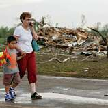 Chole Findley walks with her grandson Mark Williams as they leave the area where their home was destroyed  after the tornado hit the area near 149th and Drexel on Monday, May 20, 2013 in Oklahoma City, Okla.(AP Photo/ The Oklahoman, Chris Landsberger)