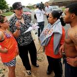 Shawna Scott, second from left, tries to help Jeanett McAllister, second from right, and McAllister's son, Tonice Woods, find McAllister's two nieces, Sabrina and Olivia Durkey, who are students at Briarwood Elementary, after a tornado struck south Oklahoma City and Moore, Okla., Monday, May 20, 2013. At left is Feliciana Hernando, Scott's niece. Scott has a home daycare near SW 156th and Vicki and went to Briarwood to pick up one of the children she watches. She took a group of students from the destroyed school to her home to wait for their parents.  (AP Photo/ The Oklahoman, Nate Billings)