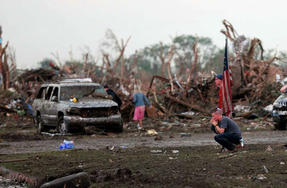 People react in front of the Plaza Towers Elementary school in Moore following a deadly tornado, Monday, May 20, 2013.  (AP Photo/ The Oklahoman, Sarah Phipps) Photo: Sarah Phipps, Associated Press / The Oklahoman