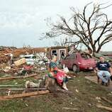 MOORE, OK - MAY 20:  (L - R) Yvonne Barragar, Joe Marshall and Barbara Garcia sit in front of Barragar's destroyed house after a powerful tornado ripped through the area on May 20, 2013 in Moore, Oklahoma. The tornado, reported to be at least EF4 strength and two miles wide, touched down in the Oklahoma City area on Monday killing at least 51 people.