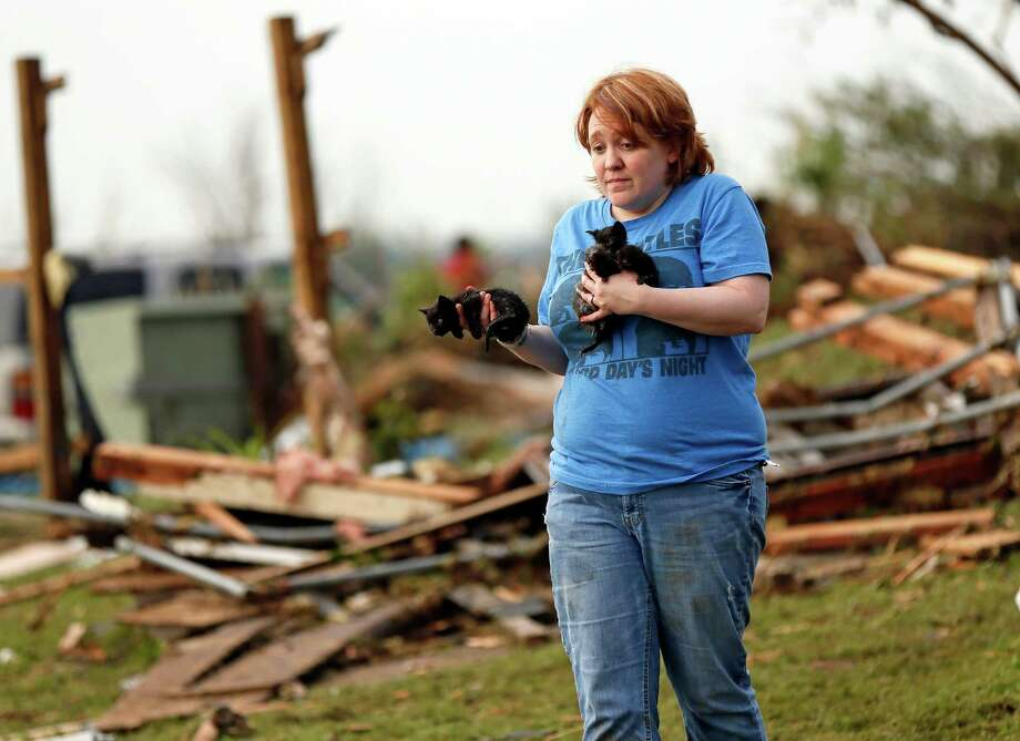 Rachel Hilton holds stray kittens she found in the debris of her parents' home at SW 149th and Stone Meadows Dr. after a tornado struck south Oklahoma City and Moore, Okla., Monday, May 20, 2013. (AP Photo/The Oklahoman, Nate Billings) Photo: Nate Billings, Associated Press / The Oklahoman