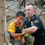 A boy is pulled from beneath a collapsed wall at the Plaza Towers Elementary School following a tornado in Moore, Okla., Monday, May 20, 2013.