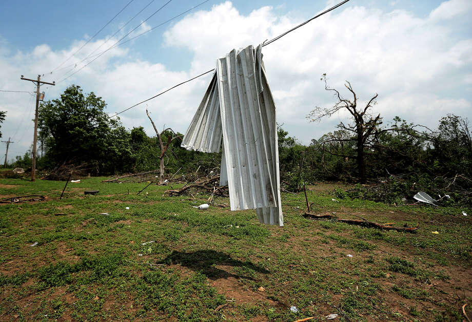 A piece of corrugated tin is draped over a power line after a tornado May 20, 2013 near Shawnee, Oklahoma. A series of tornados moved across central Oklahoma May 19, killing two people and injuring at least 21. Photo: Brett Deering, Getty Images / 2013 Getty Images