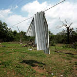 A piece of corrugated tin is draped over a power line after a tornado May 20, 2013 near Shawnee, Oklahoma. A series of tornados moved across central Oklahoma May 19, killing two people and injuring at least 21.