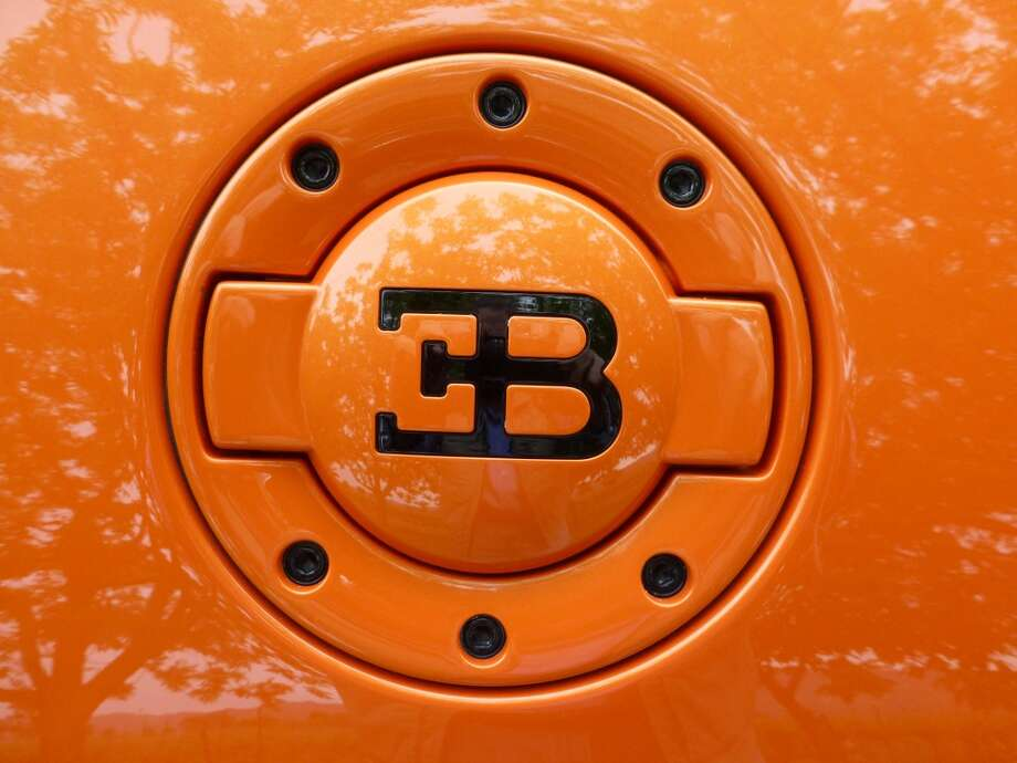 The car has a fuel filler door on the passenger side and an oil filler door on the driver's side. Both have the stylized initials of Ettore Bugatti (1881-1947), the automobile designer who founded the eponymous firm in Molsheim, France, in 1909.