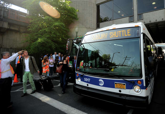 Train commuters board a bus for South Norwalk at the Bridgeport train station in Bridgeport, Conn. on Tuesday, May 21, 2013. Train service is currently suspended between Bridgeport and South Norwalk due to damage caused by Friday's Metro North train derailment and collision. Photo: Brian A. Pounds / Connecticut Post
