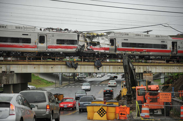 Metro North train cars heavily damaged in Friday's derailment cross Fairfield Avenue in Bridgeport, Conn. as they are pulled from the scene on Sunday, May 19, 2013. Photo: Brian A. Pounds / Connecticut Post