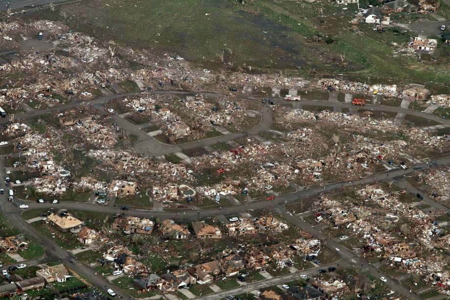 This aerial photo shows the remains of homes hit by a massive tornado in Moore, Okla., Monday May 20, 2013. A tornado roared through the Oklahoma City suburbs Monday, flattening entire neighborhoods, setting buildings on fire and landing a direct blow on an elementary school. (AP Photo/Steve Gooch) Photo: Steve Gooch, Associated Press / AP