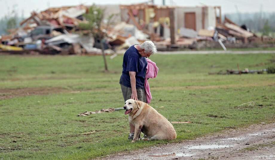 Kay Taylor stands with her dog Bailey in front of her house that was destroyed after the tornado that hit the area near 149th and Drexel on Monday, May 20, 2013 in Oklahoma City, Okla.  (AP Photo/ The Oklahoman, Chris Landsberger) Photo: CHRIS LANDSBERGER, Associated Press / The Oklahoman