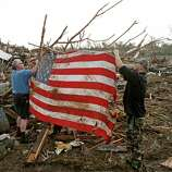 Clark Gardner, at left, and another man place an American flag on debris in a neighborhood off of Telephone Road in Moore, Okla., after a tornado moved through the area on Monday, May 20, 2013. (AP Photo/ The Oklahoman, Bryan Terry)