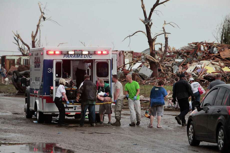 A tornado victim is loaded in an ambulance on Robinson and 142 in south Oklahoma City, Okla., Monday,  May 20, 2013.   (AP Photo/ The Oklahoman,  David McDaniel) Photo: David McDaniel, Associated Press / The Oklahoman
