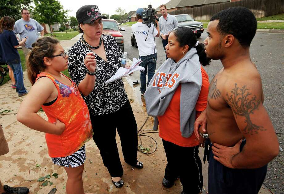 Shawna Scott, second from left, tries to help Jeanett McAllister, second from right, and McAllister's son, Tonice Woods, find McAllister's two nieces, Sabrina and Olivia Durkey, who are students at Briarwood Elementary, after a tornado struck south Oklahoma City and Moore, Okla., Monday, May 20, 2013. At left is Feliciana Hernando, Scott's niece. Scott has a home daycare near SW 156th and Vicki and went to Briarwood to pick up one of the children she watches. She took a group of students from the destroyed school to her home to wait for their parents.  (AP Photo/ The Oklahoman, Nate Billings) Photo: NATE BILLINGS, Associated Press / The Oklahoman