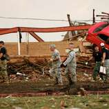 Workers walk past the rubble of Plaza Towers Elementary School after a tornado moved through Moore, Okla., Monday, May 20, 2013. (AP Photo Sue Ogrocki)