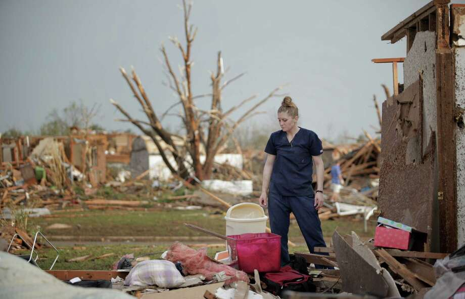 MOORE, OK- MAY 20:  Dana Ulepich looks at the debris from her house destroyed by a powerful tornado ripped through the area on May 20, 2013 in Moore, Oklahoma. The tornado, reported to be at least EF4 strength and two miles wide, touched down in the Oklahoma City area on Monday killing at least 51 people. Photo: Brett Deering, Getty Images / 2013 Getty Images