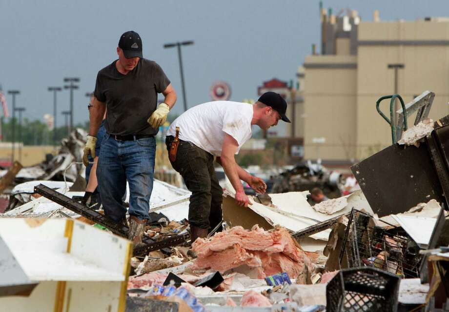 People search the debris near Telephone Road and SW 4th Street in Moore, Okla. after a tornado on Monday, May 20, 2013. (AP Photo/Alonzo Adams) Photo: Alonzo Adams, Associated Press / FR159426 AP